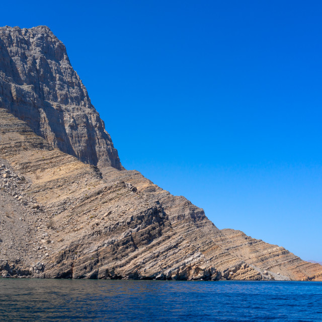 """Dhow sailing in the fjords in front of mountains, Musandam Governorate,..."" stock image"