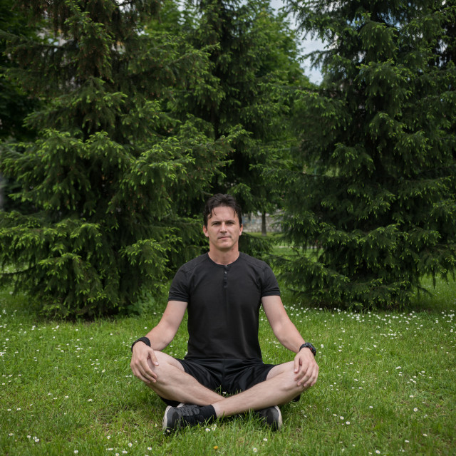 """young man meditating in nature"" stock image"