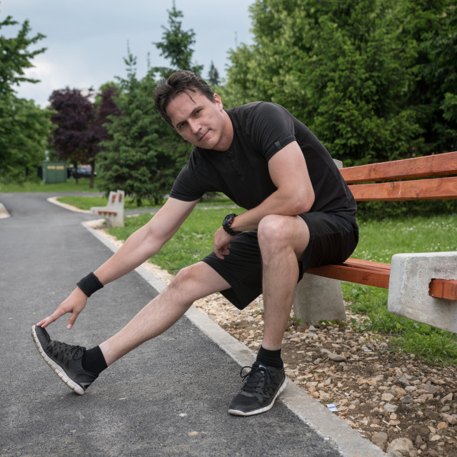 """young man stretching just before the run"" stock image"