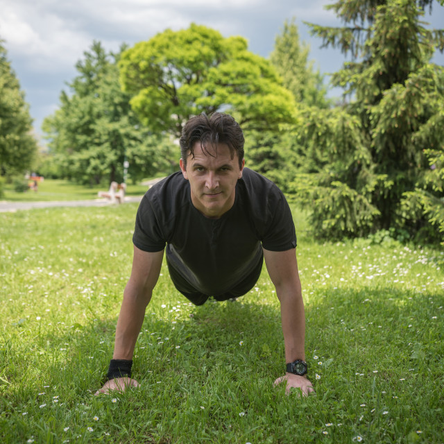 """man doing push-up in park"" stock image"
