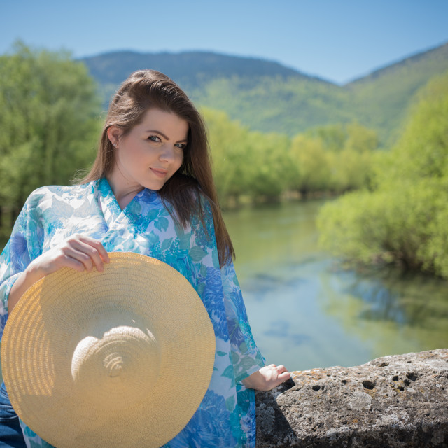 """young woman on river side holding hat in hand"" stock image"