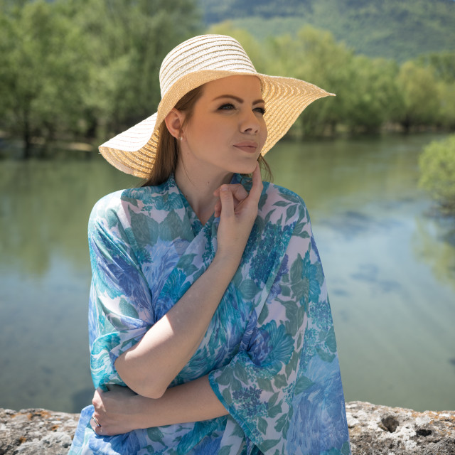 """lady standing near the wall on river side and enjoying in sunny day"" stock image"