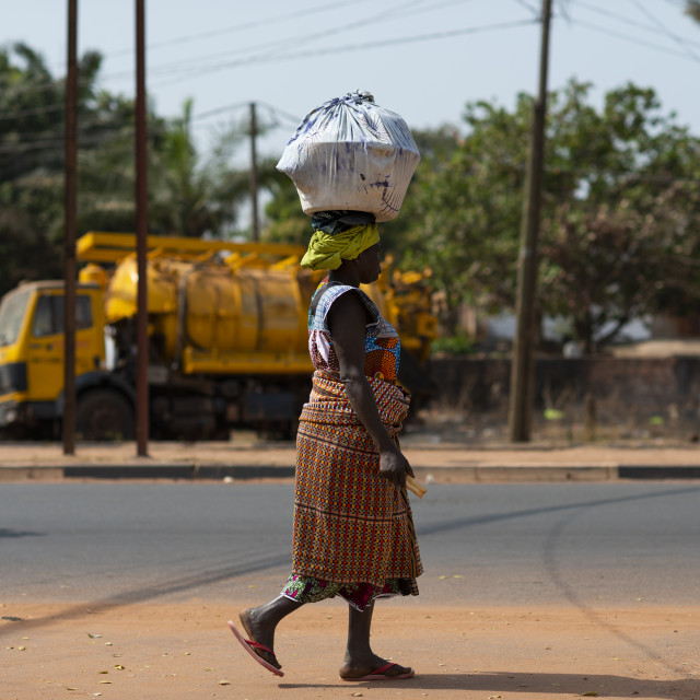 """Bissau, Republic of Guinea-Bissau - January 31, 2018: Street scene in the city of Bissau with a woman wearing a colorful dress walking in a street and carrying a tray on her head, in Guinea-Bissau, West Africa"" stock image"