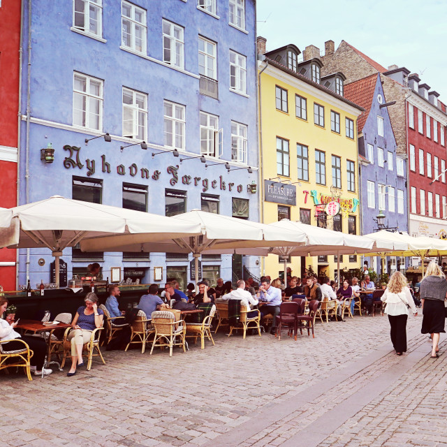 """COPENHAGEN, DENMARK - MAY 15, 2018 Panoramic view of Nyhavn harbor waterfront with bars and restaurants, famous touristic landmark and entertainment district of Copenhagen, flanked by colorful antique houses"" stock image"