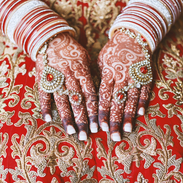 """""""The hands of Indian bride with menhdi (henna) tattoo and bunch of glitter bangles on her wrist, close-up"""" stock image"""