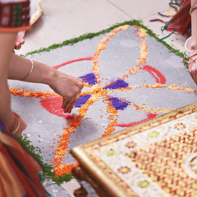"""""""Women help coloring the traditional rice art (Rangoli) on the floor for indian wedding"""" stock image"""