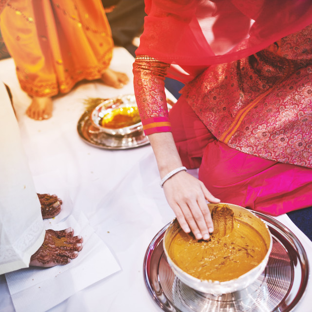 """""""Women preparaing for pasting the turmeric (haldi) oil mixed with milk on bride's feet and body"""" stock image"""