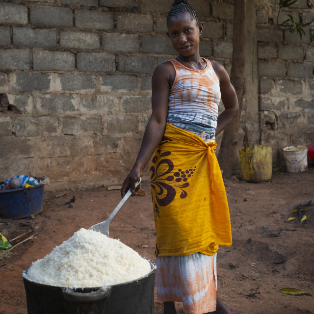 """Bissau, Republic of Guinea-Bissau - January 31, 2018: Young woman cooking rice in an old pan, at the Cupelon de Cima neighborhood in the city of Bissau, Guinea Bissau."" stock image"