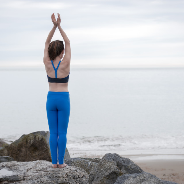 """""""woman standing on rocks by the sea practicing yoga and meditating"""" stock image"""