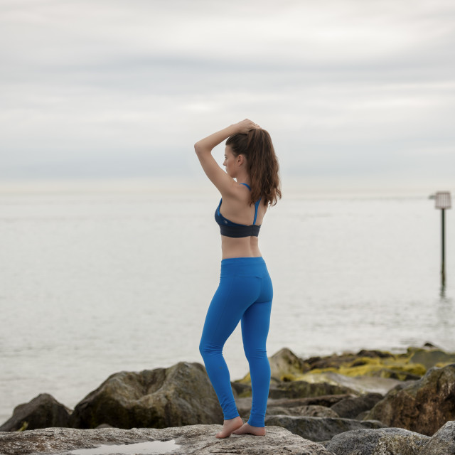 """""""sporty woman wearing sportswear standing on rocks by the sea adjusting her hair before exercise."""" stock image"""