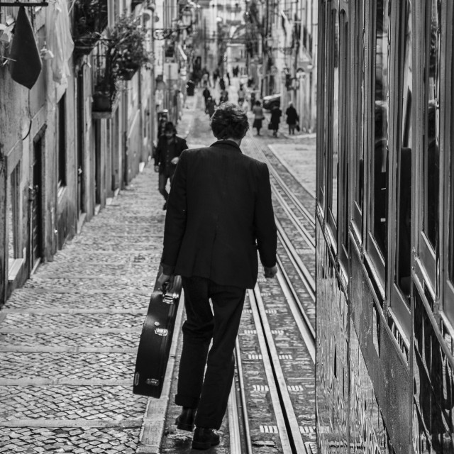 """Lisbon, Portugal - January 23, 2010: Stree scene in the city of Lisbon with a man carrying a guitar case walking down the Bica street."" stock image"
