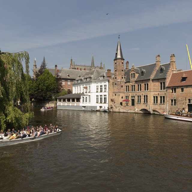 """""""Views of a canal in the city of Bruges with tourists taking a boat ride."""" stock image"""