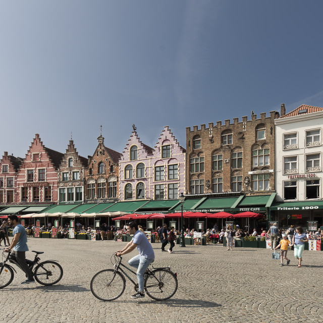 """""""Views of the market square in the city of Bruges with people going by bike in..."""" stock image"""