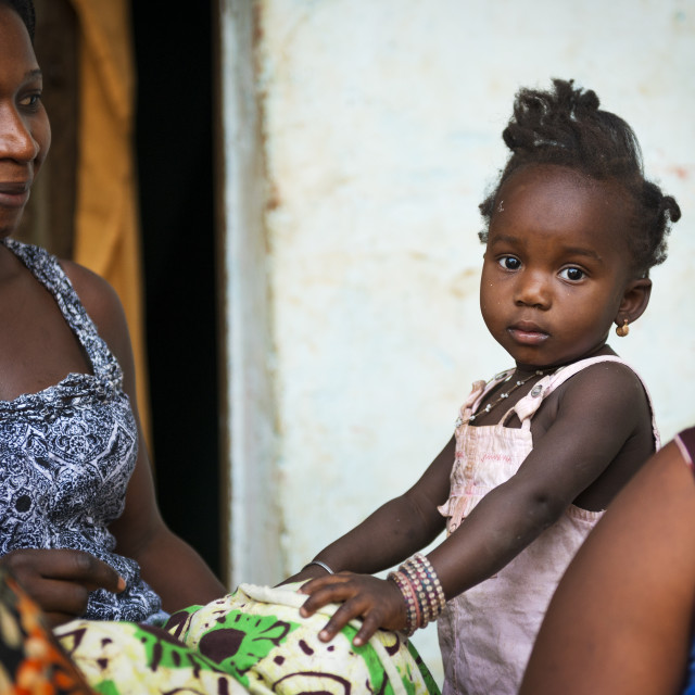 """Bissau, Republic of Guinea-Bissau - January 31, 2018: Portrait of a mother and her baby daughter at the Cupelon de Cima neighborhood in the city of Bissau, Guinea Bissau."" stock image"
