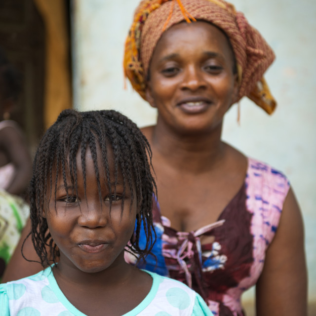 """Bissau, Republic of Guinea-Bissau - January 31, 2018: Portrait of young girl and her mother at the Cupelon de Cima neighborhood in the city of Bissau, Guinea Bissau."" stock image"