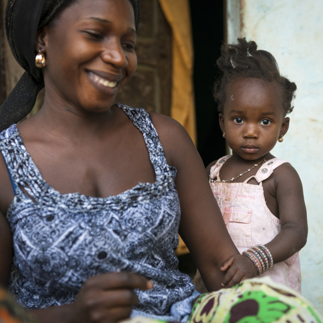 """Bissau, Republic of Guinea-Bissau - January 31, 2018: Portrait of a mother and her baby daughter at the Cupelon de Cima neighborhood in the city of Bissau, Guinea Bissau"" stock image"