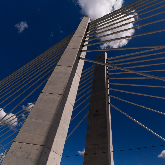 """Bridge supports in front of a cloud-speckled sky"" stock image"