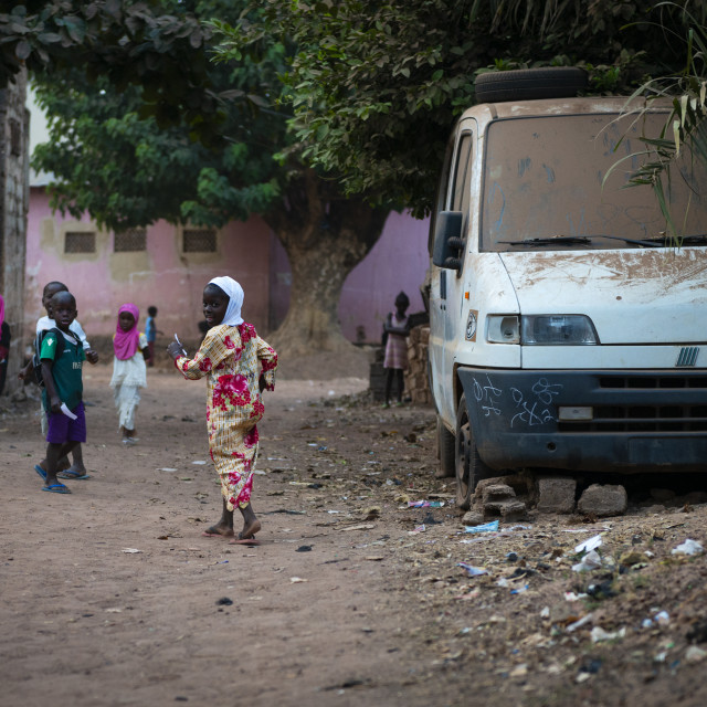 """Bissau, Republic of Guinea-Bissau - January 31, 2018: Group of children playing in dirt street at the Cupelon de Baixo neighborhood in the city of Bissau, Guinea Bissau."" stock image"