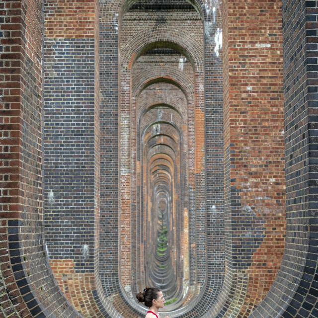 """""""woman sitting in the arches of the Ouse Valley Viaduct practicing yoga and meditating"""" stock image"""