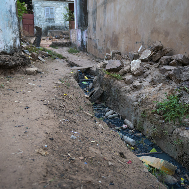 """Open air sewer along a street at the Cupelon de Baixo neighborhood in the city of Bissau, Guinea Bissau. Guinea Bissau is one of the poorest countries in the world and the public health conditions are very poor even at its capital city."" stock image"
