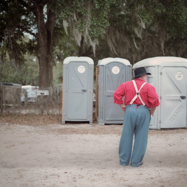 """Man waiting for toilet at Civil War reenactment in Mt. Dora, Florida USA"" stock image"