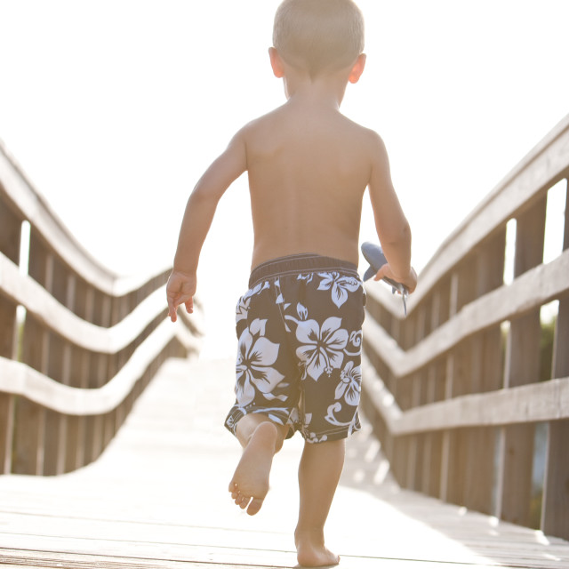 """Boy running on dock"" stock image"
