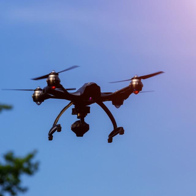 """Drone or UAV flying overhead in blue sky"" stock image"
