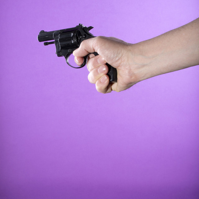 """""""Revolver in a man's hand on a purple background"""" stock image"""