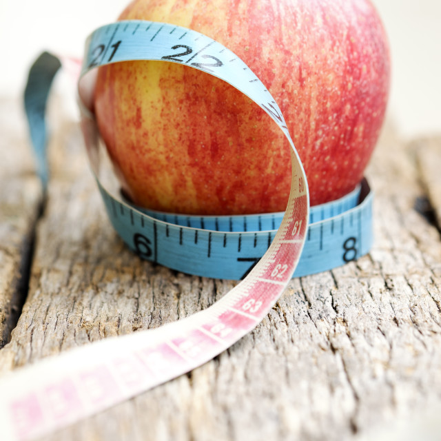 """Measuring Tape With Red Apple On Wooden Table"" stock image"