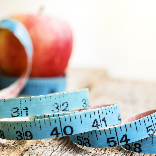 """Measurement tape with red apple in background"" stock image"