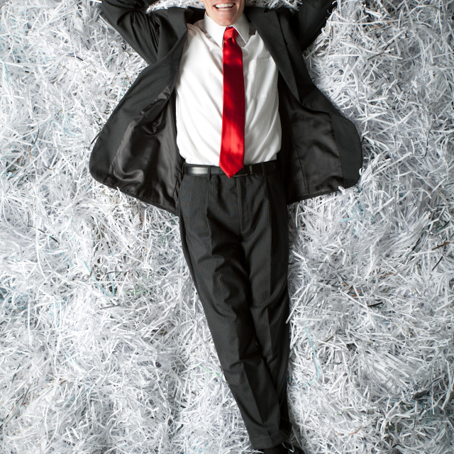 """Executive type lying on bed of shredded paper"" stock image"