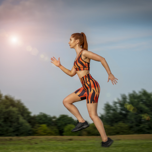 """""""woman wearing colourful sportswear running in a park"""" stock image"""