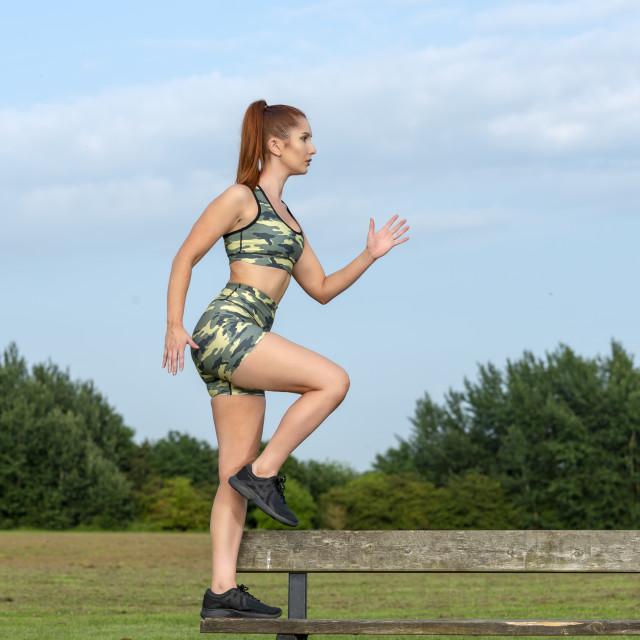 """sportswoman doing 'step ups' onto a park bench"" stock image"