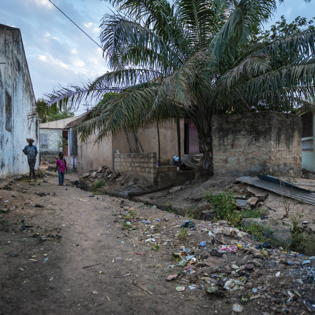 """Bissau, Republic of Guinea-Bissau - January 31, 2018: Two boys walking in a dirt street along an open sewre at the Cupelon de Baixo neighborhood in the city of Bissau, Guinea Bissau."" stock image"