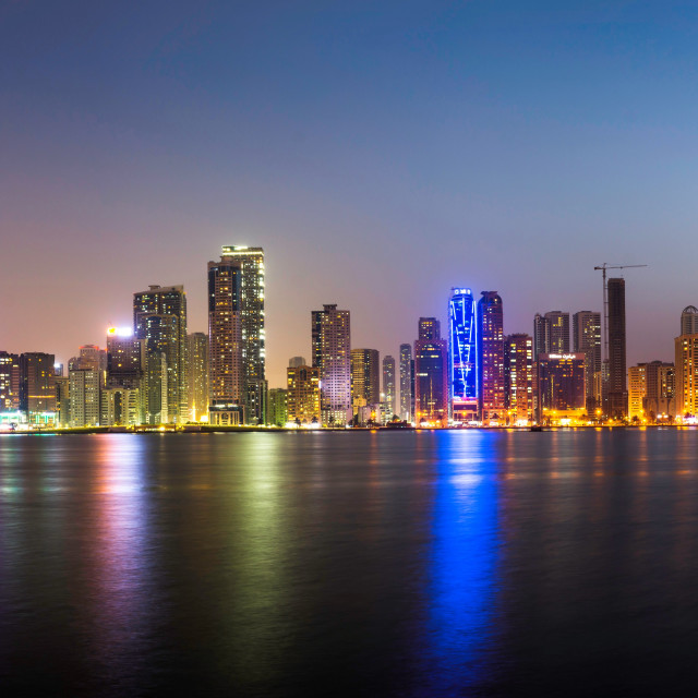 """Panoramic view of Sharjah waterfront cityscape in UAE at dusk"" stock image"