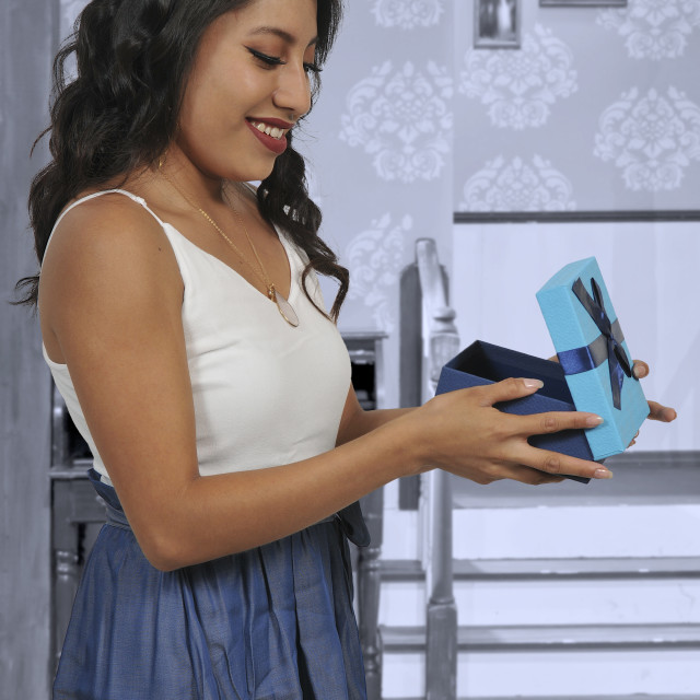 """Beautiful woman opening a present"" stock image"