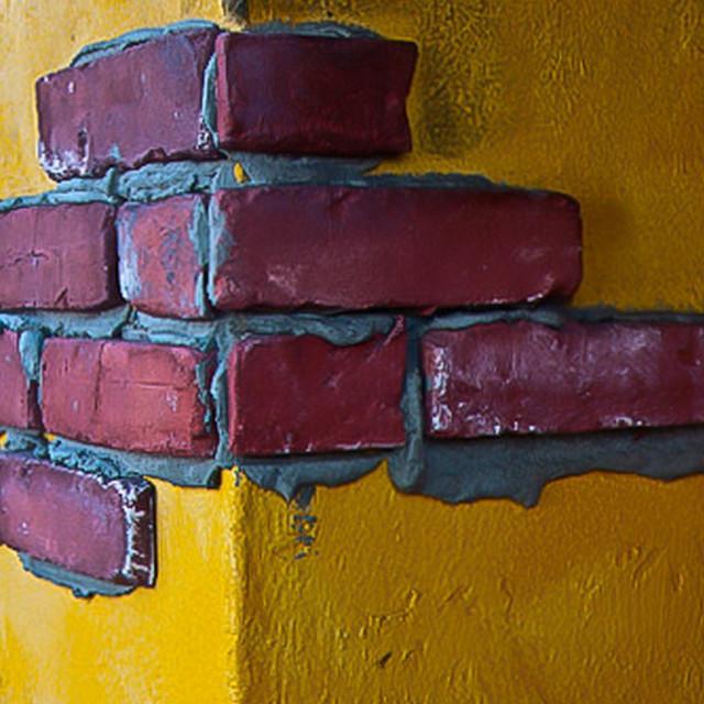 """Brown bricks on yellow wall"" stock image"