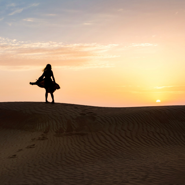 """Woman in the desert with sunset view"" stock image"