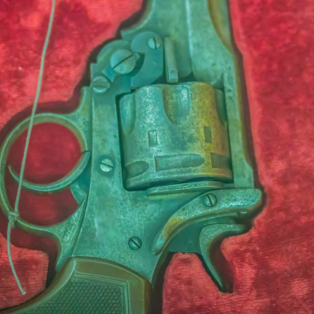 """Old short revolver gun on red box background. Vintage old pistol revolver gun."" stock image"