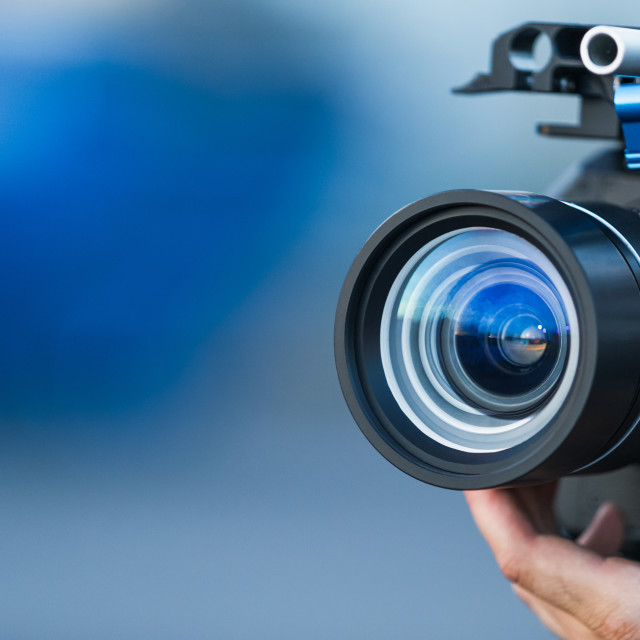 """Camera lens attached to a camera and hand focusing close up detailed with smooth blue background and sunset reflections. Concept for videography cinematography vlogging video television movies making"" stock image"