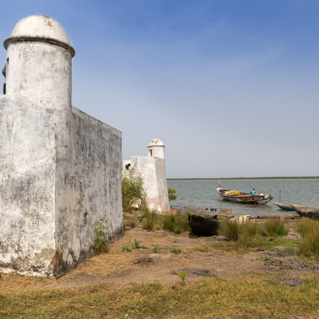 """Cacheu, Republic of Guinea-Bissau - February 1, 2018: Detail of the Cacheu Fortress and a fisherman preparing his canoe in the port of the city of Cacheu, in Guinea Bissau."" stock image"