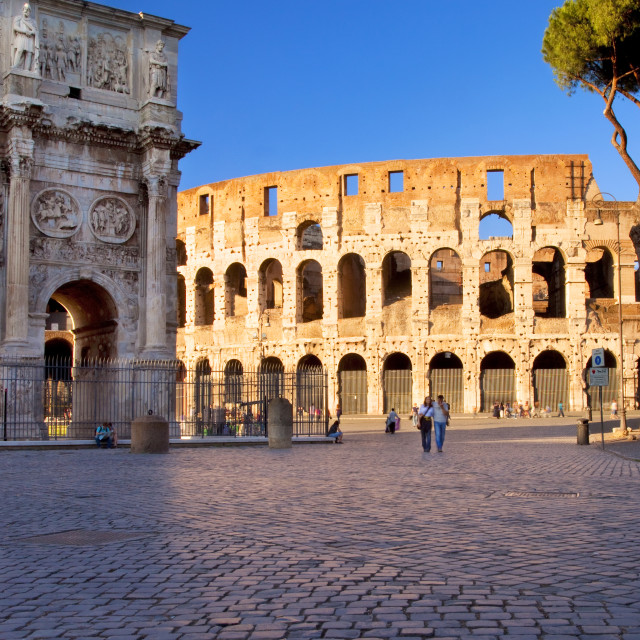 """Couple walk beside the Arco de Constantino with the Roman Coliseum beyond,..."" stock image"