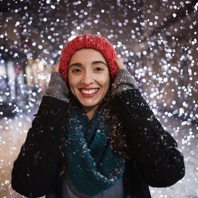 """young woman smiling on snowy night"" stock image"