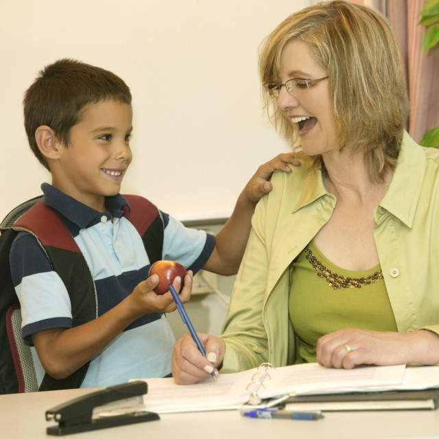"""A Young Boy Giving An Apple To His Teacher"" stock image"