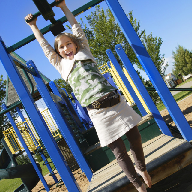 """A Young Girl Gliding Along A Playground Zip Line"" stock image"
