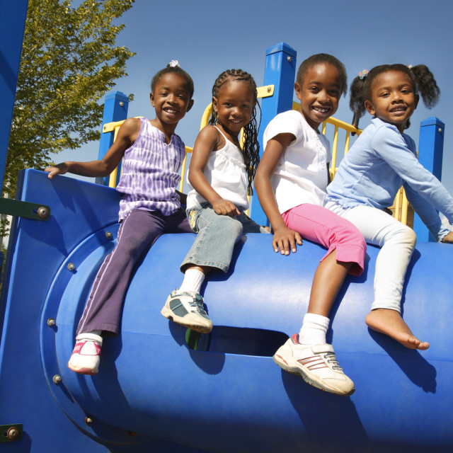 """Four Little Girls Sitting On Top Of Playground Equipment"" stock image"