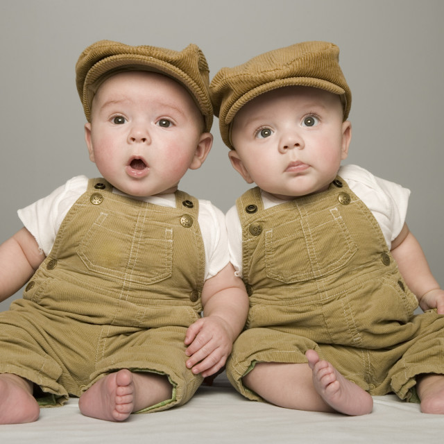 """Two Babies In Matching Hat And Overalls"" stock image"