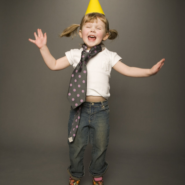 """Little Girl Jumping In Tie And Party Hat"" stock image"