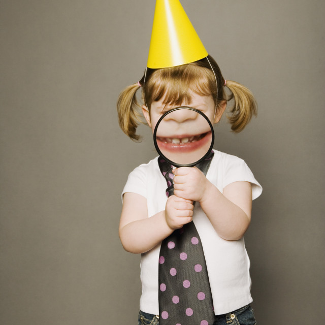 """Littly Girl In Party Hat, Holding A Magnifying Glass"" stock image"