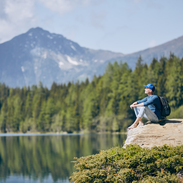 """Tourist resting on rock above lake"" stock image"